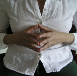 woman in white shirt, sitting with her fingertips lightly pressed together